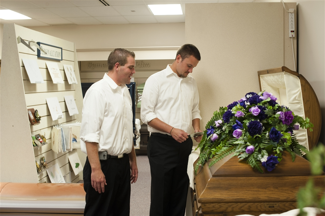 two students by casket in merchandise room