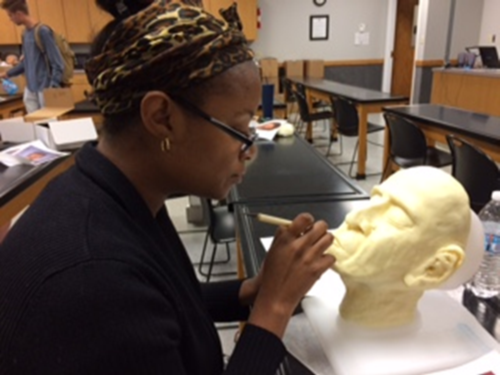 student sculpting face in restorative art classroom