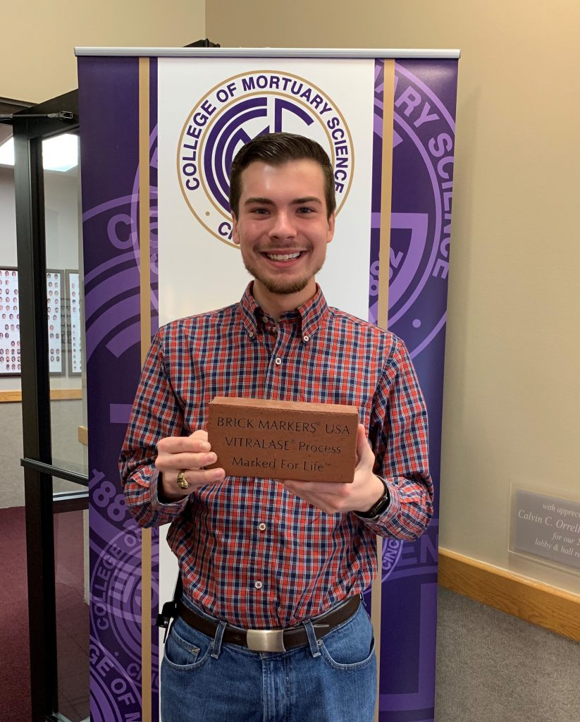 Student with engraved brick
