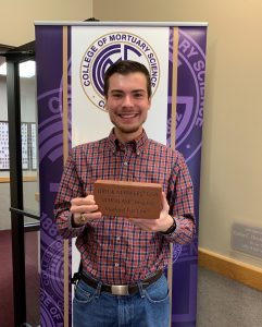 Semester 2 student Noah Saldo poses with a sample of the new commemorative bricks. His will be an 8'x8′ and include his favorite bible passage.